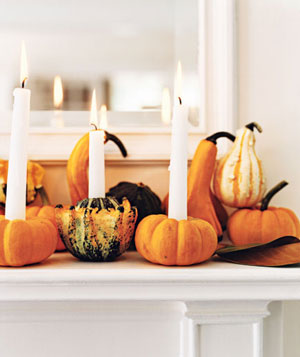 Mini gourds and pumpkins holding long candles, sitting on a white mantle