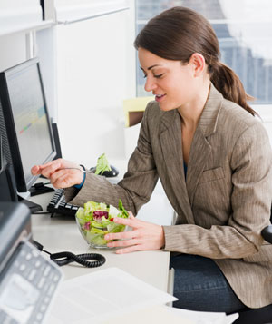 Young woman eating salad at office