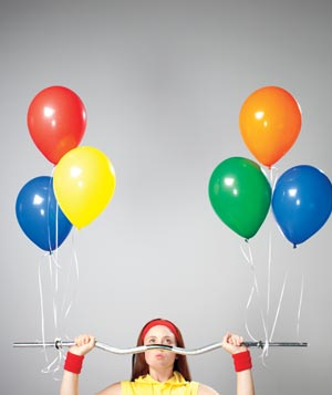 Woman lifting dumbell with helium balloons attached to it