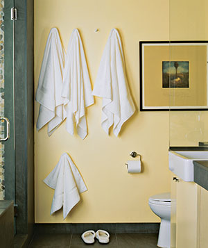 White towels hanging from hooks in a bathroom