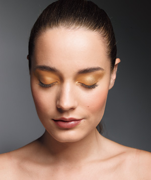 Model wearing gold eye shadow and rose lipstick