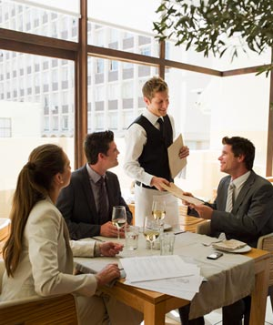 Three people looking at waiter