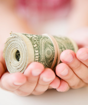Hands holding roll of money