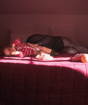 Girl laying next to mother in bed