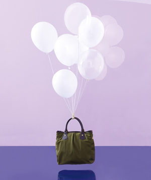Purse supported by few white balloons