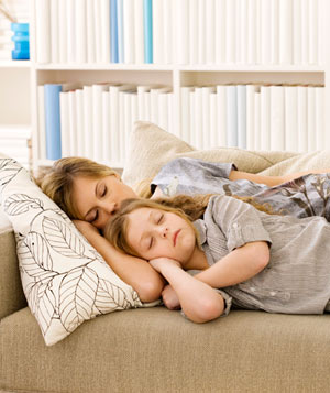 Mother and daughter napping on couch