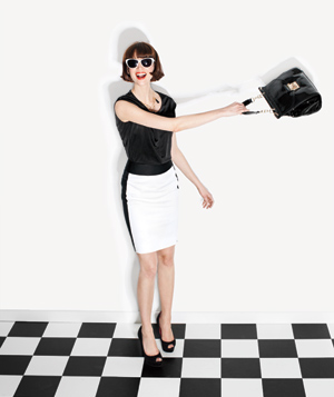 Model Wearing White Skirt and Black Top with Purse