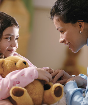 Mother with daughter holding teddy bear