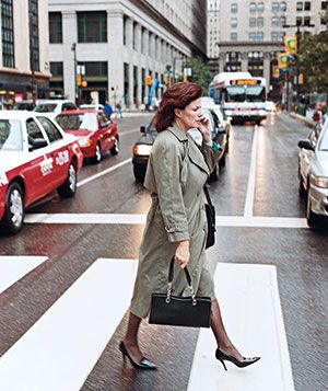 Woman crosses a road with cell phone