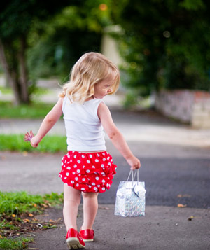 Little girl in red skirt with a goodie bag