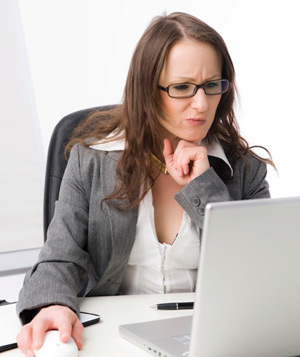 Woman looking quizzically at computer screen
