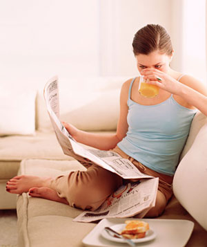 Woman reading newspaper over breakfast