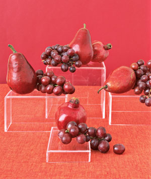 Red pears and grapes displayes on pedestals