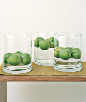Vases with green apples floating in water as centerpieces