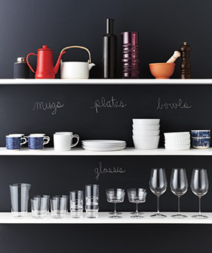 Dishes stacked on shelves in front of chalkboard wall