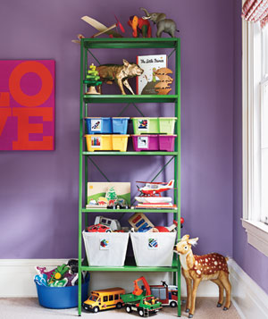Green shelf holding bins and children's toys