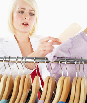 Young woman at clothes rack looking at t-shirts price tag