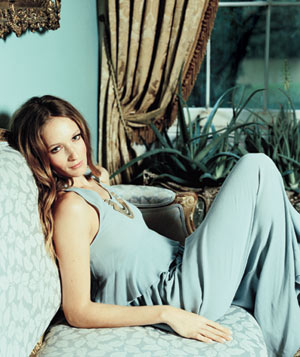 Model wearing blue maxi dress while laying on couch