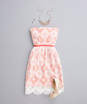Orange and white strapless lace dress with neutral heels and jewelry