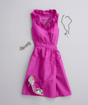 V-neck pink dress with ruffled collar, silver heels, and pendant necklace