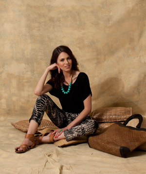 Model wearing zebra-print trousers and a teal necklace