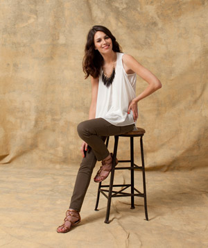 Model sitting on a stool wearing a white blouse and brown pants