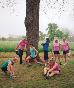 Seven female runners stretching near a tree