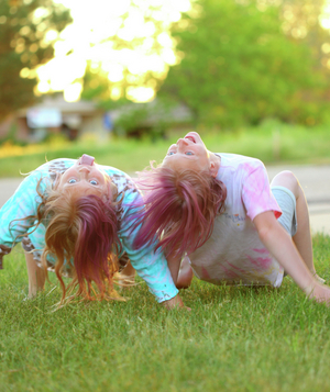 Two girls crabwalking in the grass
