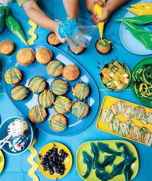 Children's party spread of decorated cupcakes and cookies on blue tablecloth