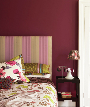 Bedroom with a red wall and patterned fabrics