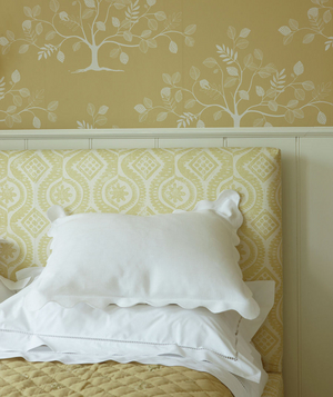 Yellow patterned headboard and wallpaper