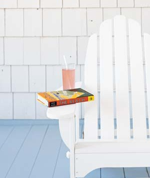 Adirondack chair with a book and a drink on a side table