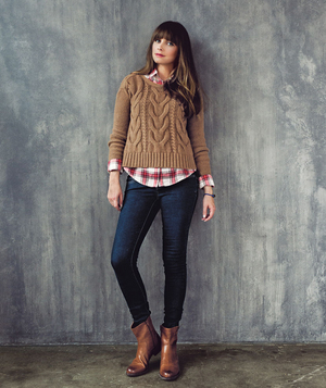 Model wearing chunky pullover sweater and faux-leather boots