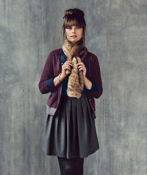 Model wearing faux-fur scarf and pleated skirt