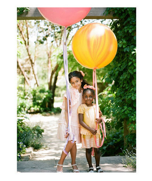 Two girls holding large balloons