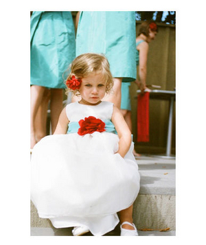 Flower girl wearing turqouise sash and red flowers