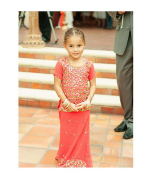 Flower girl wearing a pink lehnga with gold accessories