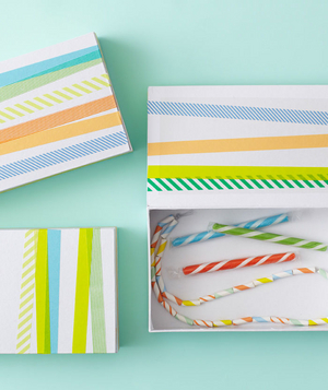 Craft boxes decorated with stripes as a birthday party favor