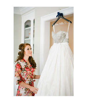 Bride looking at her hanging wedding gown