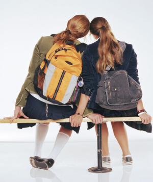 Two teenage girls sitting on a bench
