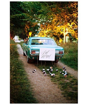 Blue car trailing cans and a just married sign
