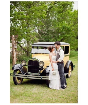 Newlyweds standing near an old yellow car
