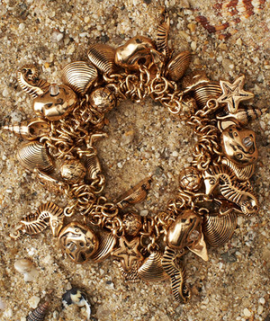 Gold charm bracelet in the sand