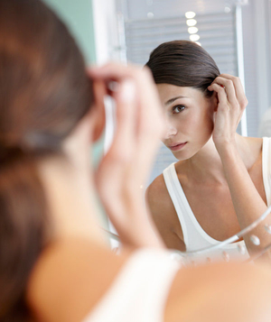 Woman looking at her hair in the mirror