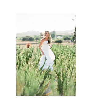 Bride smiling and walking through a field of grass