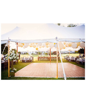 Outdoor wedding reception tent with yellow and white lanterns