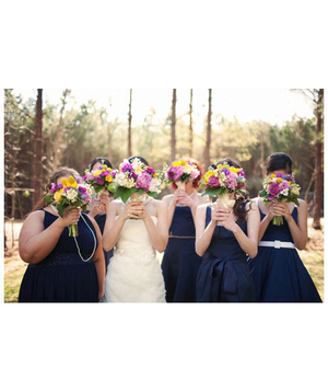 Bridesmaids and bride holding bouquets over their faces
