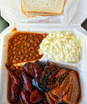 Boxed meal of barbecued beef and sausage with bread and beans