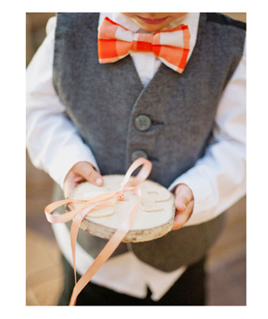 A boy ring bearer holds  slice of wood with ribbon