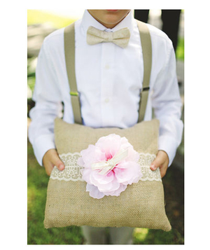 A boy holds a ring pillow made of burlap, tied with lace